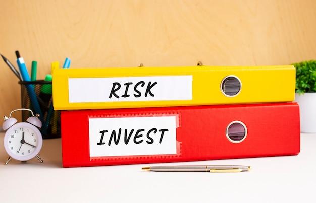 Pastas vermelhas e amarelas estão na mesa do escritório ao lado do relógio e da caneta. inscrições nas pastas risk e invest.