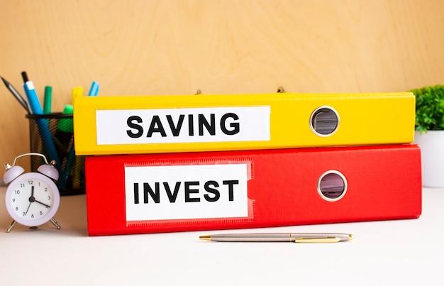 Pastas vermelhas e amarelas estão na mesa do escritório ao lado do relógio e da caneta. inscrições nas pastas saving e invest.