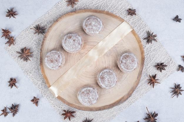 Pastéis doces com anis estrelado seco em prato de madeira