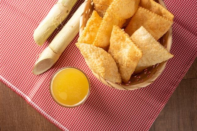 Pastéis fritos brasileiros, um copo de caldo de cana e canas posicionadas sobre uma toalha de mesa quadriculada