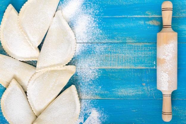 Pastéis na fritos não na farinha sobre uma mesa de madeira azul. prato tradicional turco-mongol. produtos semi-acabados congelados. espaço livre para uma inscrição.