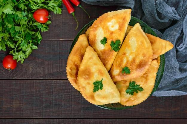 Pastéis na pastagem dourados suculentos em uma tabela de madeira. prato tradicional turco-mongol. comida de rua. bistro.