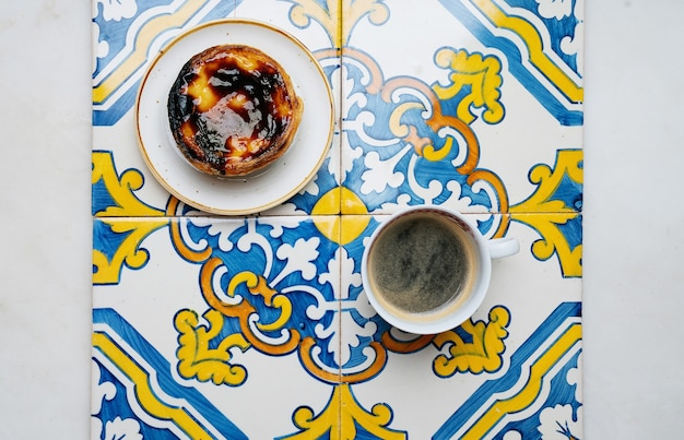 Pastel de nata. sobremesa tradicional portuguesa, torta de ovo e café sobre azulejos tradicionais do azulejo. vista do topo