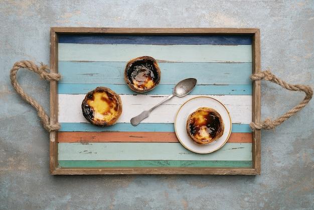 Pastel de nata. sobremesa tradicional portuguesa, torta de ovo na bandeja de madeira com fundo rústico. vista do topo
