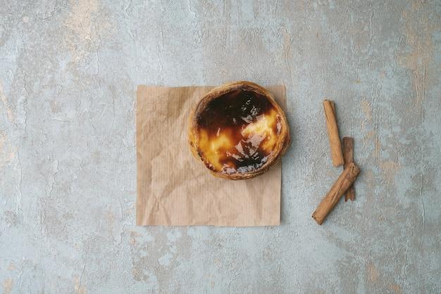 Pastel de nata. sobremesa tradicional portuguesa, torta de ovo na folha de papel manteiga sobre um fundo rústico com paus de canela. vista do topo