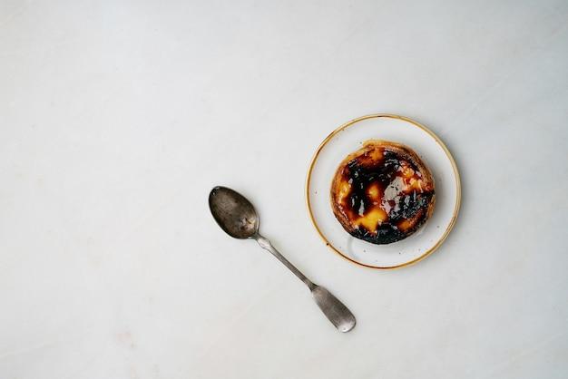 Pastel de nata. sobremesa tradicional portuguesa, torta de ovo no prato de cerâmica com uma colher sobre fundo de mármore. vista do topo