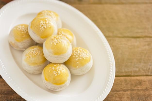 Pastel escamoso chinês ou bolo da lua cheio de pasta de feijão mungo doce e gema de ovo salgada na chapa branca
