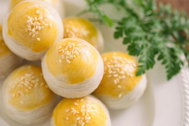 Pastel escamoso chinês ou mooncake cheio de pasta de feijão mungo doce e gema de ovo salgada na chapa branca