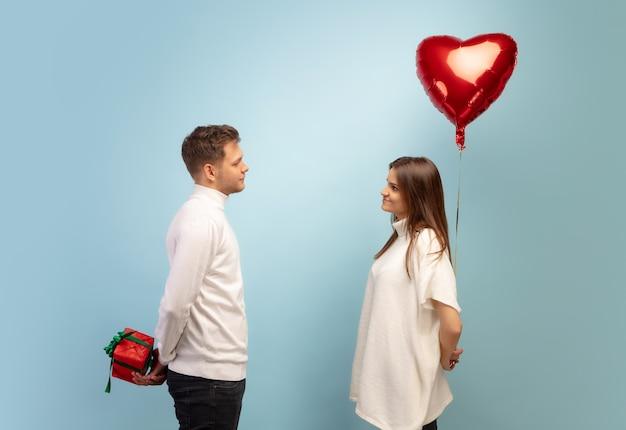 Pastel. lindo casal apaixonado em fundo azul do estúdio. dia de são valentim, amor, relacionamento e conceito de emoções humanas. copyspace. jovem e mulher parecem felizes juntos.