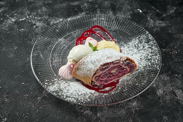 Pastelaria austríaca clássica - strudel de massa folhada com cerejas, nozes e sorvete em uma mesa escura. close up, foco seletivo