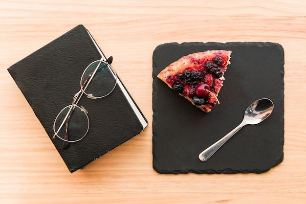 Pastelaria berry perto de diário e óculos na mesa de madeira