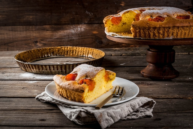 Pastelaria caseira de outono e verão. pão de ló com damascos. corte em pedaços, prato, garfo. no stand. na velha mesa rústica de madeira. copie o espaço