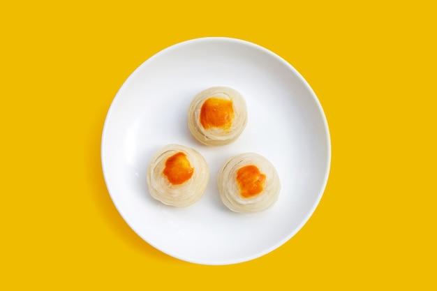 Pastelaria chinesa em chapa branca sobre fundo amarelo.