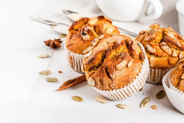 Pastelaria de outono e inverno. muffins de abóbora saudáveis com especiarias tradicionais de outono, sementes de abóbora. com uma xícara de chá. mesa de mármore branco