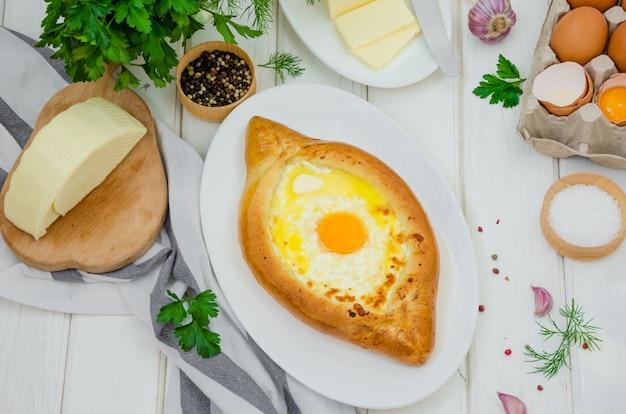 Pastelaria de queijo georgiano tradicional de ajarian khachapuri com ovos e manteiga num prato sobre uma superfície de madeira branca