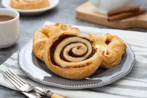 Pastelaria dinamarquesa com uma xícara de café no café da manhã. pãezinhos de canela, bolos frescos no café da manhã. copie o espaço.