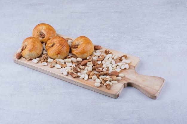 Pastelaria doce com miolo na placa de madeira com várias nozes.