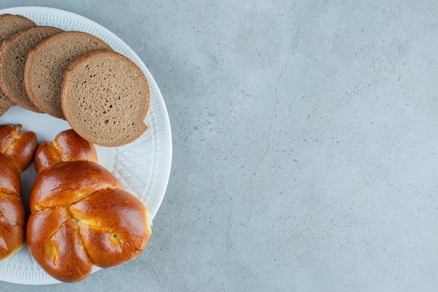 Pastelaria doce e fatias de pão na chapa branca.