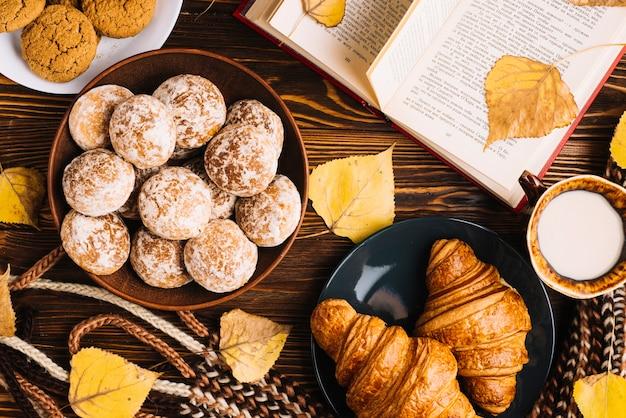 Pastelaria e leite perto de cachecol e livro