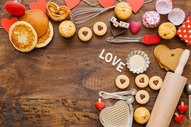 Pastelaria e utensílios de cozinha em mesa de madeira