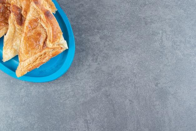 Pastelaria em forma de triângulo cheia de queijo na placa azul.