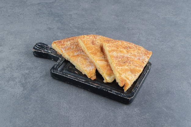 Pastelaria em forma de triângulo na placa de corte preta.