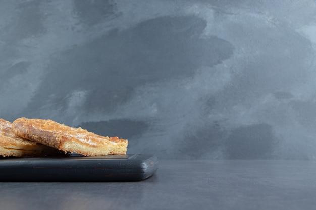 Pastelaria em forma de triângulo no quadro escuro.
