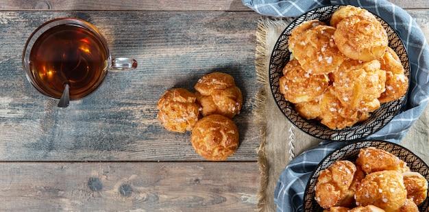 Pastelaria francesa choux e chá na mesa de madeira