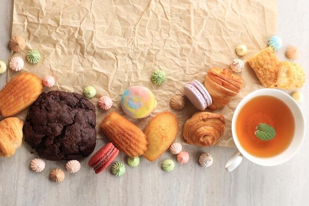 Pastelaria francesa variada com cópia espaço na mesa de mármore branco para texto ou receita. macaroons, merengue, madeleine, craquelin eclair, mini croissant, big chocolate cookies e a cup of tea
