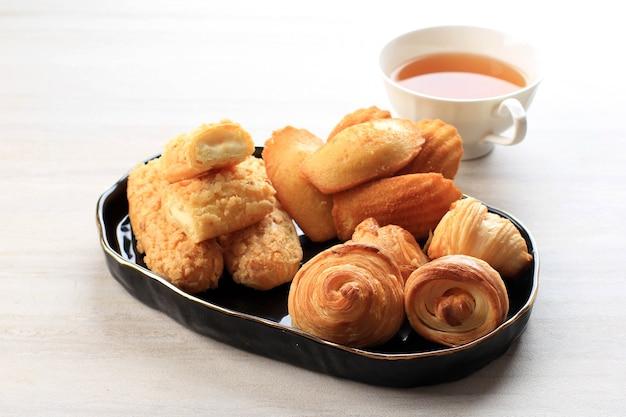 Pastelaria francesa variada com espaço de cópia na mesa de mármore branco para texto ou receita e uma xícara de chá