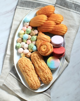 Pastelaria francesa variada na mesa de mármore branco para texto ou receita. macaroons, merengue, madeleine, craquelin eclair, mini croissant, big chocolate cookies