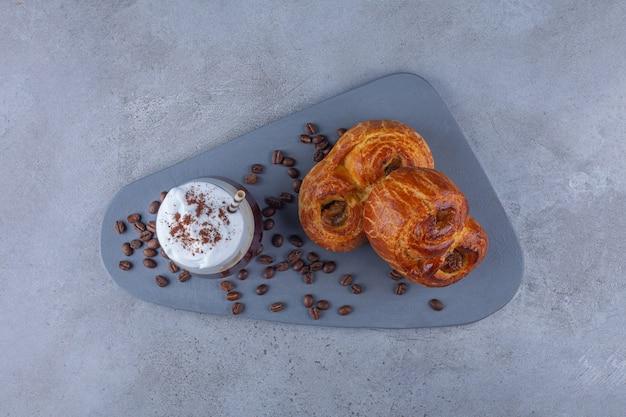 Pastelaria fresca com copo de café e grãos de café na placa de madeira.