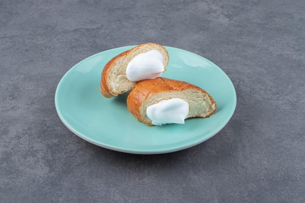 Pastelaria fresca com creme na placa azul.