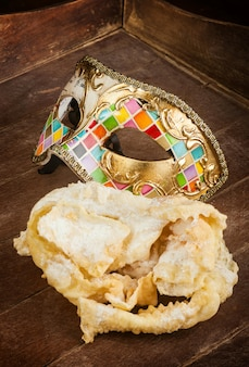 Pastelaria fritada do carnaval italiano com máscara venetian.