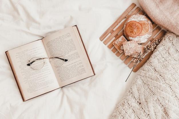Pastelaria, óculos deitado no livro aberto na cama