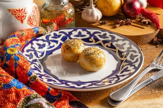 Pastelaria oriental samosa. tortinhas recheadas com carne picada, cebola e molho, cobertas com mel e polvilhadas com sementes de papoula.
