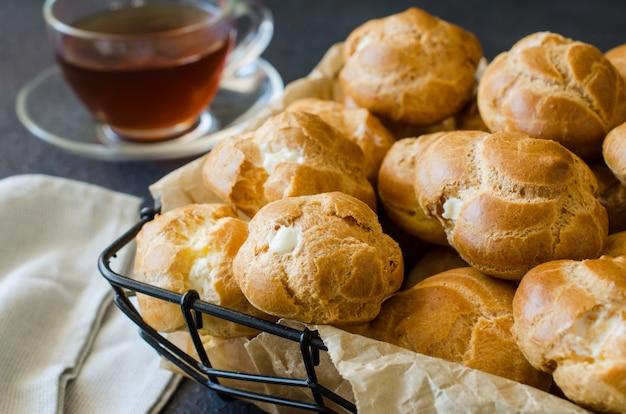 Pastelaria profitroles caseira cheia de creme. eclairs com creme, sobremesa francesa.