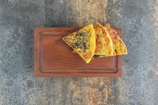 Pastelaria triangular com sementes de papoula em uma placa de madeira