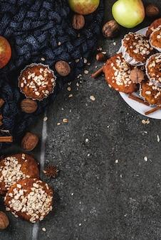 Pastelarias de outono inverno. comida vegana. biscoitos caseiros saudáveis, muffins com nozes, maçãs, flocos de aveia. ambiente acolhedor, cobertor quente, ingredientes. mesa de pedra escura. vista do topo