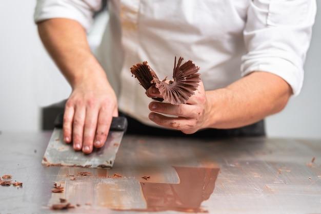 Pasteleiro profissional que faz doces do chocolate na loja dos confeitos.