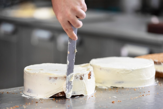 Pasteleiro profissional que faz um bolo delicioso na loja de pastelaria.