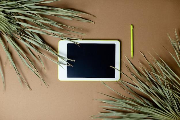 Pastilha branca com caneta no fundo de papel ofício. escritório em casa enquanto auto-isolamento, trabalhando em casa. educação on-line, e-learning em quarentena. folhas de palmeira secas em papel ofício.