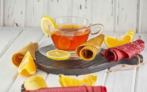 Pastilha doce de frutas puras em rolinhos com frutas cítricas e chá com limão. doces saudáveis -