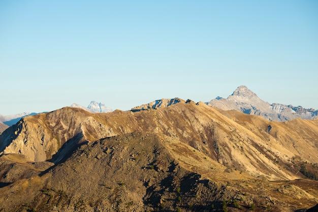 Pasto da alta altitude, picos de montanha rochosa e cume entalhado, com céu cênico, os alpes italianos. visão expansiva em luz de fundo. imagem desaturated tonificada.