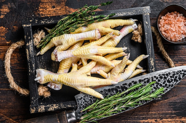 Patas de frango cru na tábua de cortar açougueiro com faca. fundo de madeira escuro. vista do topo.