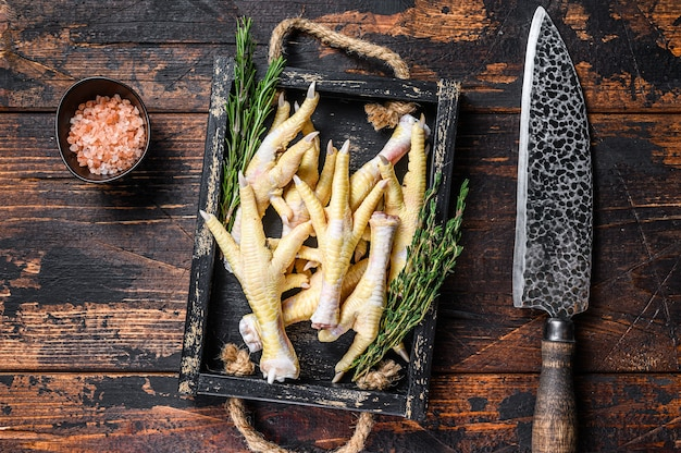 Patas de frango cru na tábua de cortar açougueiro com faca