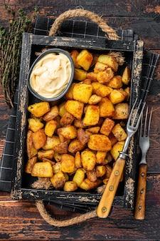 Patatas bravas batatas tradicionais espanholas petiscos de tapas. fundo de madeira escuro. vista do topo.