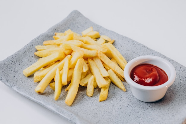 Patatos fritos com ketchup isolado
