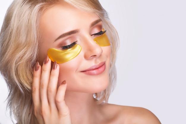 Patch sob os olhos. rosto de mulher bonita com manchas de hidrogel ouro