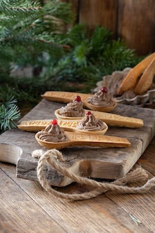 Patê de fígado de frango caseiro com cranberry em colheres de biscoitos comestíveis na tábua de madeira velha